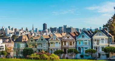 Zeitraffer mit viktorianischen Häusern in der Steiner Street mit der Skyline von San Francisco dahinter.