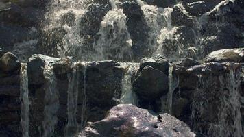 cascada de montaña. Cerca de agua cayendo sobre piedras en cámara lenta