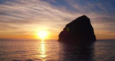 vista aérea do pôr do sol refletindo no incrível padrão de água da poça de maré na praia no noroeste do Pacífico