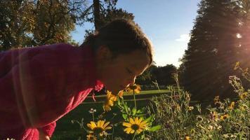 Niña se inclina para oler flores silvestres otoñales
