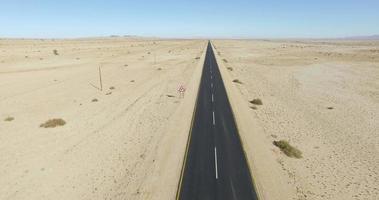 4K Aerial view of straight tar road through the Namib desert