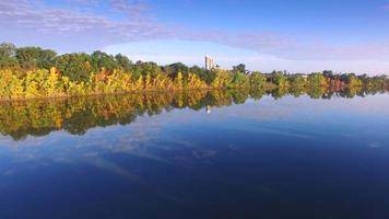 sobrevoo da folhagem colorida de outono na beira de um rio pitoresco