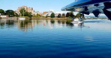 hidroavião táxi no porto, avião gêmeo, reflexo na água ainda azul video