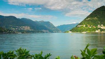 Italia giornata di sole como lago baia verdi montagna costa panorama 4K lasso di tempo video