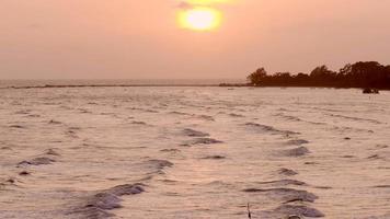 ondas na praia ao pôr do sol