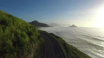drone feito vista aérea ao longo da costa junto ao mar, onde existe uma ciclovia para prática de esportes automotivos enquanto se aprecia a natureza e a paz, feita em resolução 4k