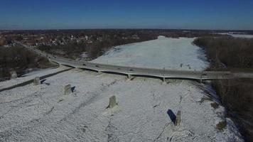 Aerial view of bridge over frozen river as traffic passes over