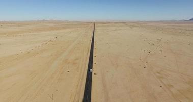 4k Luftaufnahme des Autos, das auf gerader Teerstraße durch die Namibwüste fährt
