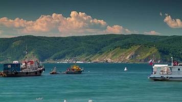 Russia giornata di sole baikal lago costa barca sole luce nuvole 4k lasso di tempo video