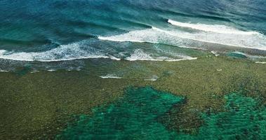 Luftaufnahme, die über Korallenriff fliegt und Meereswellen bricht
