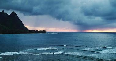 Luftaufnahme, die über Ozeanriff und Wellen in dramatischen Sonnenuntergangssturm am Nordufer von Kauai fliegt