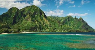 Luftaufnahme, die über tropische Korallenrifflagune in Richtung schöner grüner Berge fliegt