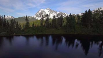 Panorâmica panorâmica do lago da floresta com fundo do pico da montanha nevada video