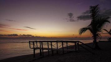 ponte de madeira e a palmeira na praia perto do oceano nascer do sol timelapse