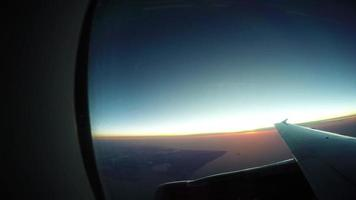 4k die Sonne steigt hinter dem Horizont auf - ein Blick vom Flugzeug im Flug