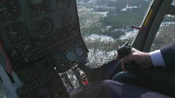 View control system pilot hold lever of helicopter. Camera in pilot cabin. Above forest. Sunny. Snow video