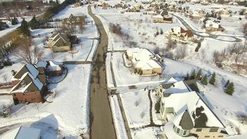 Wealthy suburban homes blanketed in winter snow, aerial view video
