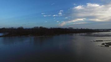 Hermosa cámara de apertura moviéndose sobre el agua hacia la isla revelando el cielo azul video