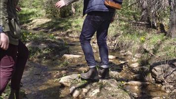 petit ami et petite amie sautant par-dessus le ruisseau