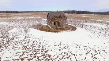 kleine alte Hausruinen im gefrorenen Bauernfeld.