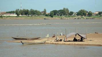 Les pêcheurs assis sous une bâche sur le banc de sable de la rivière
