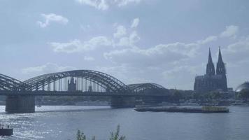 barco passando pela catedral de colônia e sob a ponte hohenzollern em 4k e slog3. koelner dom. Tiro longo. video
