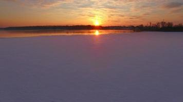 Amazingly colorful sunrise over icy water surface, low aerial view video