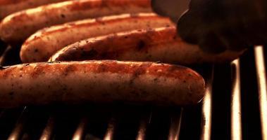 salsichas em um churrasco ao ar livre sendo viradas
