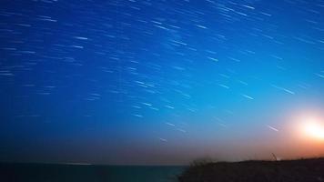 estrelas e lua sobre o mar. lapso de tempo uhd video