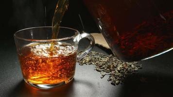 Llene de té caliente a una taza de una tetera