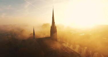 la cámara vuela hacia una iglesia cubierta de niebla