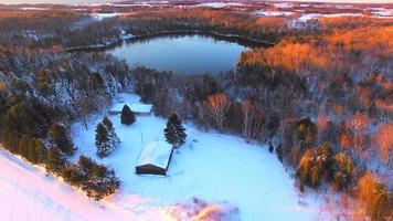 schneebedeckte Wälder umgeben den eisigen See im Morgengrauen