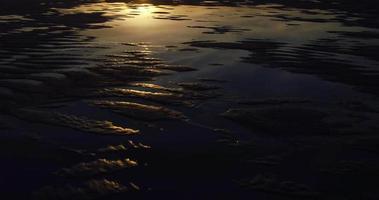 Vista aérea del atardecer reflejándose en el increíble patrón de agua de la piscina de marea en la playa en el noroeste del Pacífico video