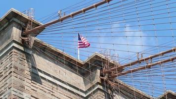 bandiera degli Stati Uniti che ondeggia sul lasso di tempo di ponte di brooklyn 4K da New York