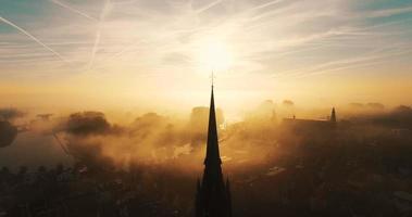 Una silueta de la torre de una iglesia temprano en la mañana con mucha niebla. video
