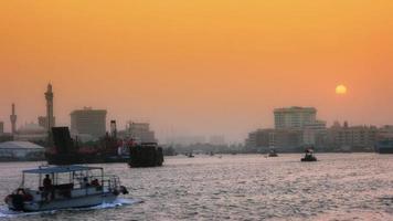 foto fechada de uma balsa se movendo no rio ao anoitecer, dubai, emirados árabes unidos