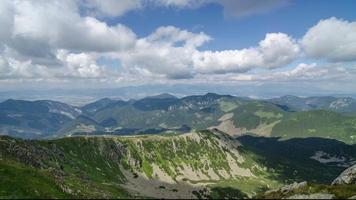 mooie witte wolken en luchten vliegen over groene bergen landschap time-lapse