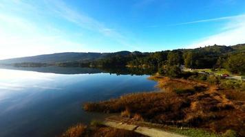 cielo azul espejo reflectante superficie del lago de vidrio con hierba verde y marrón costa y la autopista 92 con tráfico que pasa por vista aérea 4k estabilizada vista de pájaro ultra alta definición volando gopro hero4 siguiendo hacia el punto arbolado. video