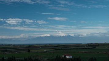 vista de timelapse de uma paisagem pitoresca com o Monte Olimpo e o campo contra nuvens no céu azul, Grécia video