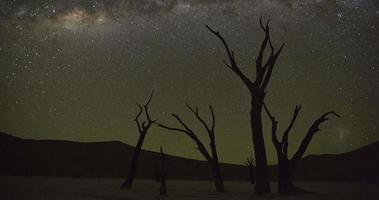 4k lapso de tempo do pôr da lua e as estrelas se movendo no céu em sossusvlei, dentro do parque nacional namib-naukluft