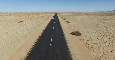 4k vue aérienne de la voiture roulant sur route goudronnée tout droit à travers le désert du namib