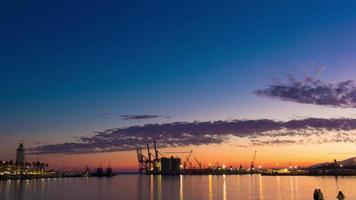 espagne coucher de soleil ciel clair malaga port et phare panorama 4k time lapse