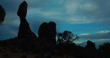 Zeitrafferaufnahme eines ausgeglichenen Felsens mit Kletterern oben, Bögen Nationalpark in der Nähe von Moab, Utah, USA