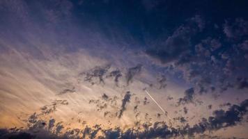 lasso di tempo di percorsi a getto attraverso il tramonto con le nuvole