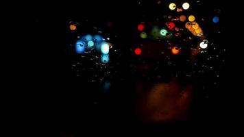 semafori notturni sfocati attraverso il parabrezza bagnato