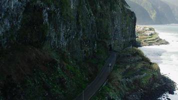 Car Going Near the Sea Along Mountain Slopes. Aerial Shot from Madeira. video