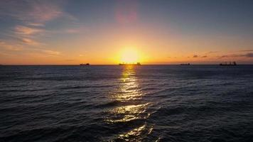 Luftbild über Meerwasser, Frachtschiffen und wunderschönem Sonnenaufgang