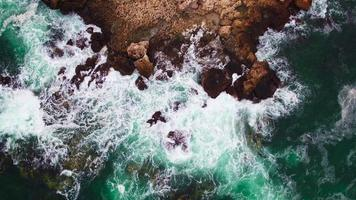 Aerial view of rocky coastline and crashing waves over cliffs