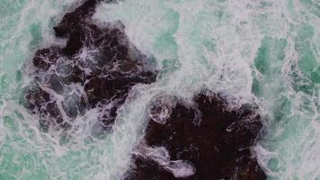 Ocean waves crashing over cliffs, aerial view
