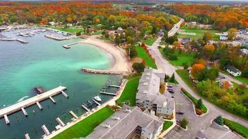 voando sobre docas coloridas de outono à beira-mar, praia e copas de árvores video